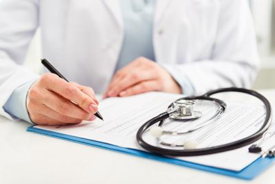 Arzt schreibt auf ein Blatt neben Stethoskop