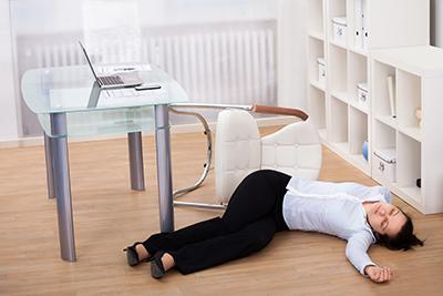 Bewusstlose Geschäftsfrau am Arbeitsplatz liegt auf dem Boden