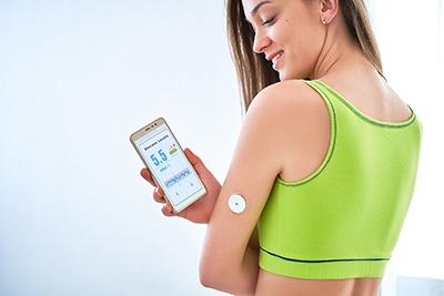 Diabetiker überprüfen den Glukosegehalt mit einem Fernsensor und Smartphone