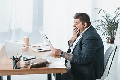Geschäftsmann in Anzug gähnt am Arbeitsplatz