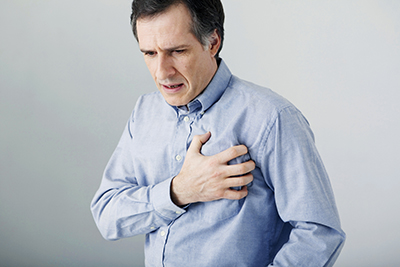 Mann greift sich an der Brust, Brustschmerzen