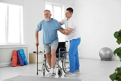 Professioneller Physiotherapeut, der mit älteren Patienten in einem Rehabilitationszentrum arbeitet